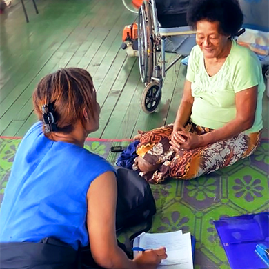 Two women sit together on a blanket on the floor, talking. One woman is writing on paper. A wheelchair sits unoccupied behind the other woman.