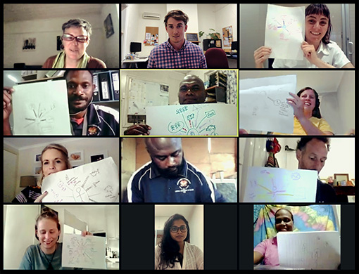 12 people on a video call are holding up pieces of paper with hand drawn diagrams on them to show each other.